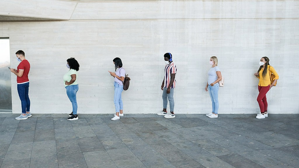 Multiracial people standing in a queue and waiting – Young people with social distancing and wearing protective face masks – Concept of the new normality and social distancing